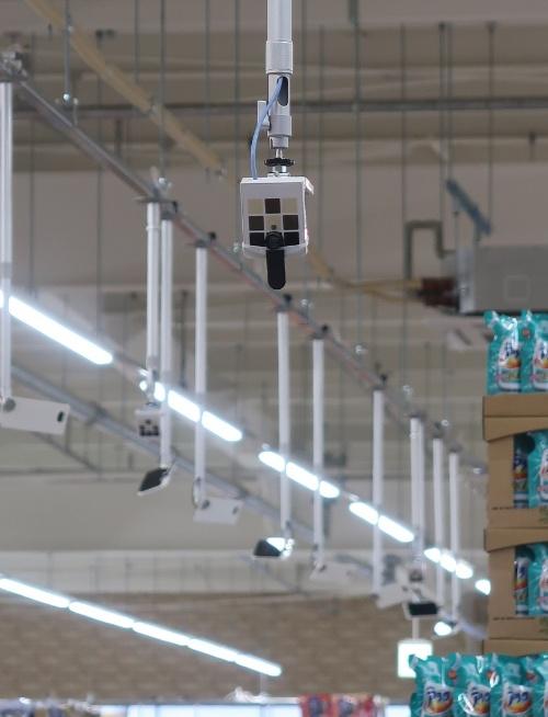 来店客を出迎える、新店入り口にある正方形のカメラ。写真後方の天井にぶら下がるのも全てカメラで、店舗全体で合計700台を設置。目的に応じて、2種類のカメラを用意した
