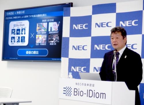 登壇した田熊範孝氏。日経 xTECHが撮影。スクリーンはNECのスライド