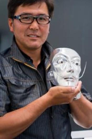 アルミを切削加工したサルバドール・ダリの面を持つ大槇精機社長の大町亮介氏。