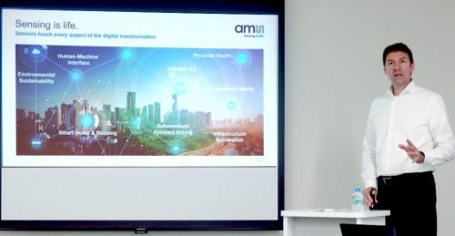 登壇したStéphane Curral氏(右端)。日経 xTECHが撮影。スクリーンはamsのスライド