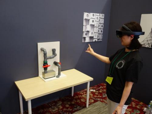 「Microsoft Remote Assist」のデモを体験している様子。HoloLensを着けた体験者が、空間に表示された写真やビデオ通話のウインドウをハンドジェスチャーで操作し、パイプについた2つのオレンジ色の栓を操作しようとしている