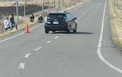 図4(a)落下物に見立てたコーンを道路上に置いた。道路がカーブした地点で、後方車両からは見通し外の状況だった