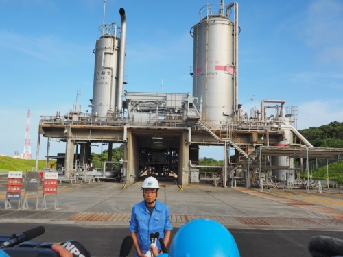 図3 試験終了後、集まった報道陣に燃焼試験の成功を伝えるJAXA第一宇宙技術部門H3プロジェクトチームプロジェクトマネージャの岡田匡史氏。後ろに見えるのが、LE-9の燃焼試験スタンド。