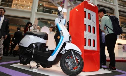 図1 台湾KYMCOの電池交換式EVバイク「Many」と充電ステーション