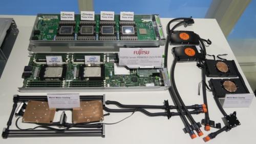 1つの計算ノードは、四つのGPUを搭載したボード(写真上)とふたつのCPUを載せたボード(写真下)から成る。右側にあるオレンジ色と黒の部品が水冷ジャケット