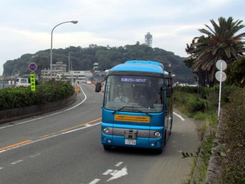 江の島を背後に走る自動運転バス