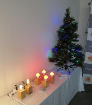 4個のIoT LED電球(中央)とクリスマスツリーのLED電飾を接続した電源タップ(右)をGoogle Homeを使って操作するデモ