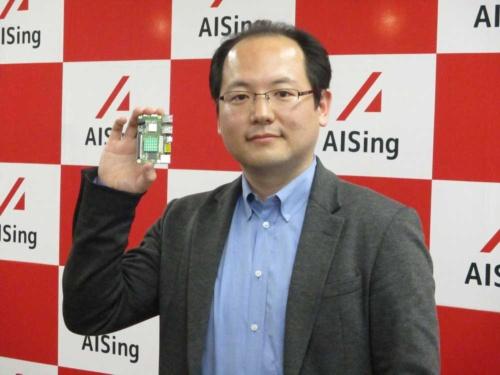 図1 エイシング代表取締役CEOの出澤純一氏 右手にあるのがAIチップ「AiiR(エアー)チップ」である。
