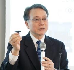 ルネサス社長兼CEOの呉文精氏。手に持っているのはIDTとルネサスのチップを組み合わせたリファレンスデザインの一例。(撮影:日経 xTECH)