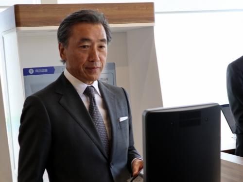 黒い顔認証センサーの前に立つファミリーマートの沢田貴司社長