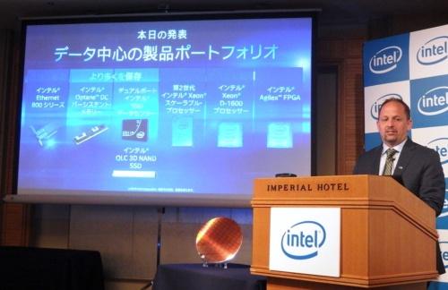 インテルが2019年4月9日に東京で開催の報道機関向けイベントに登壇したIntelのJason L. Grebe氏(右端)。7つの新製品を紹介した。スクリーンの下にあるのはXeon Platinum 9200シリーズのウエーハー。日経 xTECHが撮影。スクリーンはIntelのスライド