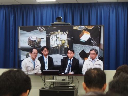 図1 記者説明会で人工クレーターの生成に成功したことを伝えるはやぶさ2プロジェクトのプロジェクトマネージャを務める津田雄一氏(ディスプレーの映像の1番左)