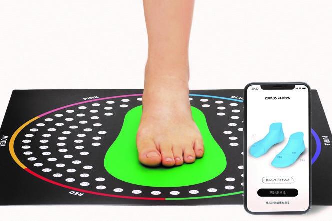 専用のマットに足を乗せ、スマートフォンを使って足のサイズを計測する