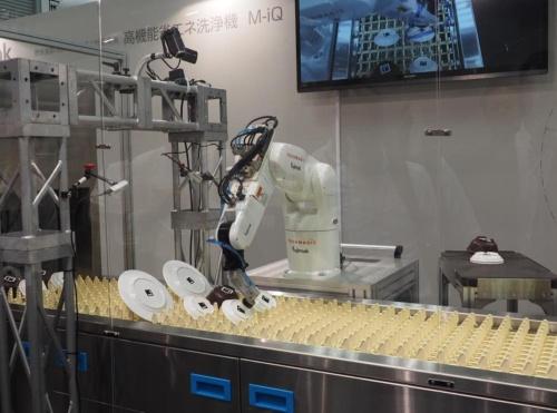 自動洗浄機のコンベア上にある食器を、ロボットハンド先端の吸引パッドを使ってピッキングするロボット。(写真:日経 xTECH)