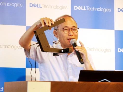 東京工業大学の佐藤誠名誉教授。右手に持つのが力覚提示装置「SPIDAR」