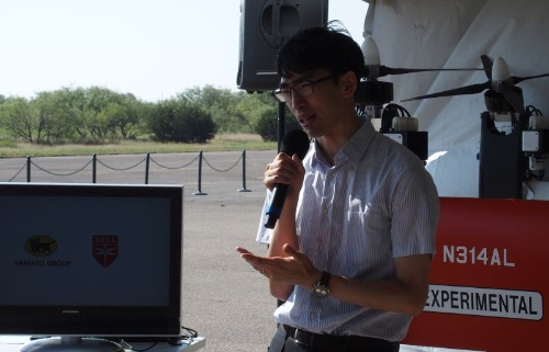 PUPAの特徴などを説明するYHDの伊藤氏。飛行デモの現場は日光が強く、まぶしかった(撮影:日経 xTECH)
