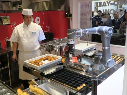 たこ焼きをピックアップしているたこ焼き調理ロボット