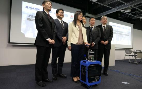 AIスーツケースの試作機と共同開発に参加する関係者。試作機に手を掛けている中央の女性は開発を主導する米IBMの浅川智恵子フェロー。