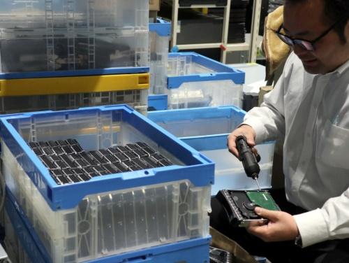 ハードウエアリサイクルを手掛けるゲットイットの倉庫で大量のHDDの金具を電動ドライバーで外すところ