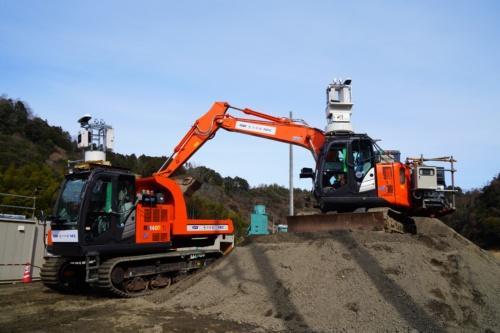 掘削した土砂を積み込む油圧ショベル(写真右)と、その土を敷きならし範囲まで運ぶクローラーキャリア(写真左)。いずれも遠隔操作で動かした