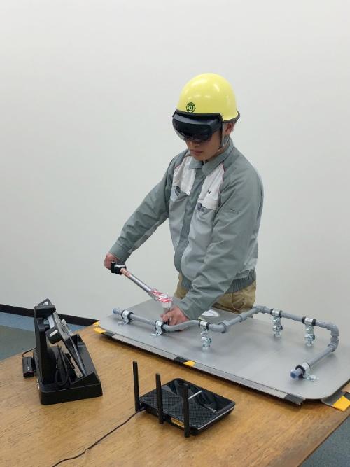 スマートグラスを装着してボルトを締結する作業者