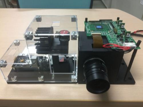 東芝の受光技術を利用した、200mの測距が可能なLiDARの試作機。左側の透明な箱に入っているのが、発振波長905nmのレーザー素子と同素子から出射する光を走査するガルバノミラーで構成した投光系。右側が受光系である。垂直、水平共に視野角が7度のCマウントのレンズを利用した。