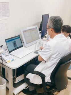 医師は、MeDaCaを使ったビデオ通話用のパソコン(左側)と、電子カルテ端末を並べてオンライン妊婦健診を行う