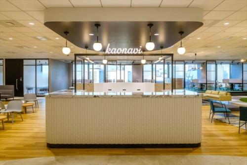 新本社オフィスの無人レセプション。背後のテーブルにはハイチェアーが並び、交流の「ハブ」とする。また、来場者がカウンター内で「kaonavi」のサインを入れて記念撮影できる体験ゾーンになっている