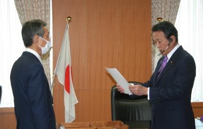 麻生太郎金融相から免許書を受け取るみんなの銀行の横田浩二頭取(左)