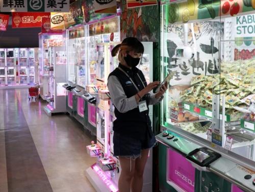 ゲームセンター「セガ新宿歌舞伎町」の店内。店員がクレーンゲーム機の前で、タブレットに表示される「連絡ノート」などの内容をチェック