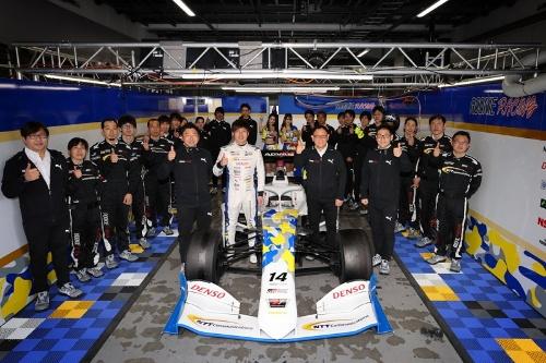富士スピードウェイで記念撮影する「NTT Communications ROOKIE」の大嶋和也選手(クルマ左、白のレーシングスーツ)と、チームオーナーであるトヨタ自動車の豊田章男社長(クルマを挟んで反対側の1人目)