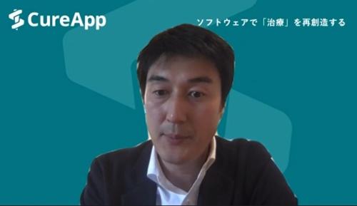 講演するCureAppの佐竹晃太 最高経営責任者(CEO)