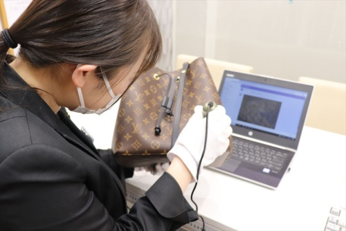 「AI真贋判定システム」を使い、バッグを調べるコメ兵の鑑定士
