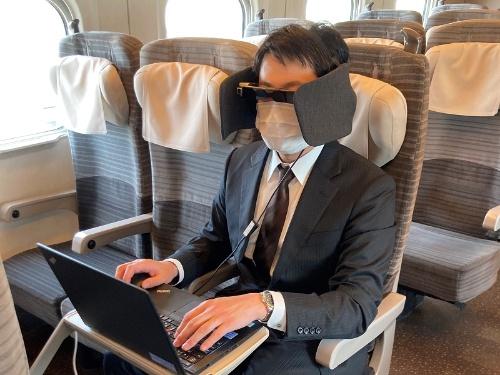 一部の列車で借りられるヘッドホンと視界と音を遮るパーティションが一体になった「WEAR SPACE」。目に装着しているのは、スマートグラス「MOVERIO」