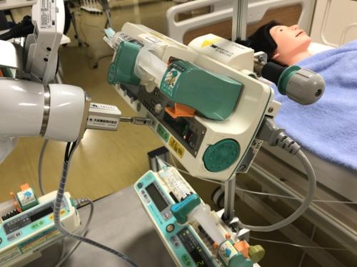 ロボットを操作してシリンジポンプのボタンを押す様子