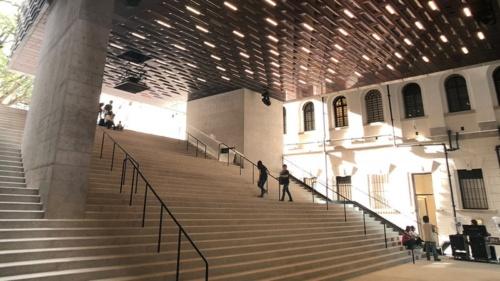 コートヤードから新築である「JCキューブ」のピロティ部分につながる大階段。「ランドリーステップ」と呼ばれる。歩行者の動線を確保しつつ、簡単な観客席のような役割も果たす(写真:©Arup)