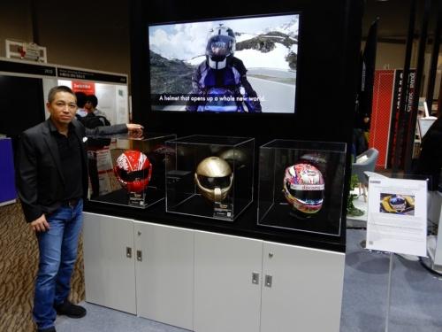 図4  HUD搭載スマートヘルメット「Sparta」(左の2つ)と、透明液晶を搭載したレーサー用ヘルメット(右)。左は、今回の展示にかける思いを語ったJDI 常務執行役員CMOの伊藤嘉明氏
