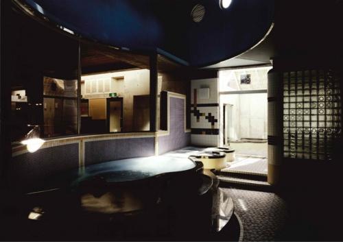 「延命湯」(1983年)の浴場。曲線の浴槽、タイル張りの内装、潜水艦をモチーフにしたトップライトなどが特徴。右手のガラスブロックの中はサウナ。外には露天風呂もある(写真:絹巻 豊)