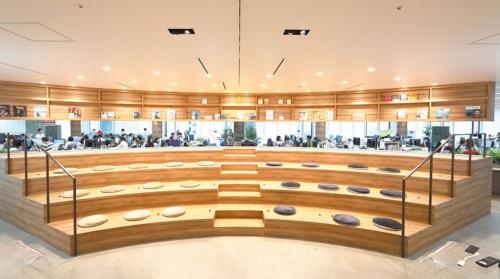 明るい色調の木材を使った半円形のステージ。天井からつり下がった形の書棚も同じ木目調のテイストに統一され、非常に美しい。訪問者は強い印象を受ける。