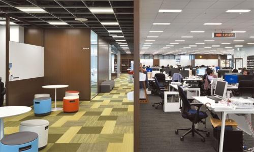 まるで合成したように見えるが、ホワイトボードや壁を中央にして撮影した一枚の写真だ。左がワイガヤスペースで右が通常の執務スペース。天井やカーペットの色調も変えた。