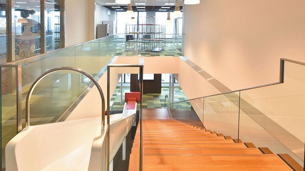 32階と31階の間にある階段とすべり台。奥にジャングルジムやブランコ型椅子を配した打ち合わせスペースが見える。