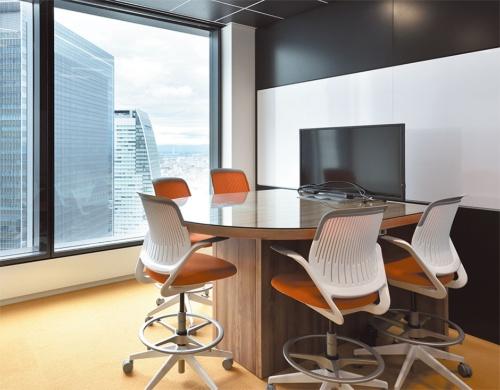 ハイテーブルとハイチェア、ディスプレーのある打ち合わせスペース。テーブルには書き込みもできる。