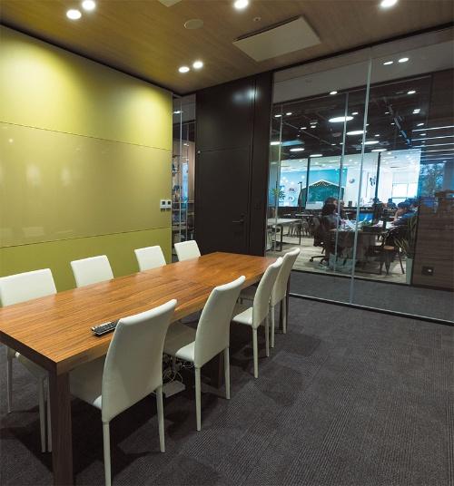 受付後ろの会議室。壁が透明になっていて、打ち合わせスペースや奥の子供用スペースまで見通せる。