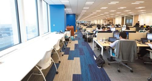 16階の執務エリアは青が基調で、内装テーマは「海」。明るい窓際にカウンター式のデスクを配置した。