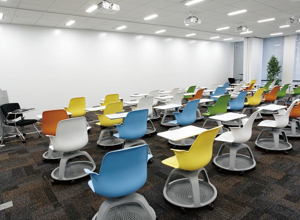 カラフルな椅子が並ぶプレゼン用ルーム。壁がホワイトボードになっている。