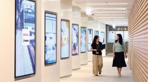 オフィス内の通路にある「Glass Partition Digital Signage」。業務提携を結ぶ企業と自社のサービス紹介も行なっている。8枚のデジタルサイネージを組み合わせた動画演出もある。