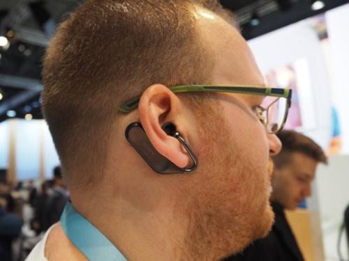 Xperia Ear Duoを装着しているところ。耳の後ろから掛ける設計となっている。人間工学に基づいており、従来よりもむしろ落下しにくいという。写真は2月26日より開催されていた、Mobile World Congress 2018のソニーモバイルブースより(筆者撮影)