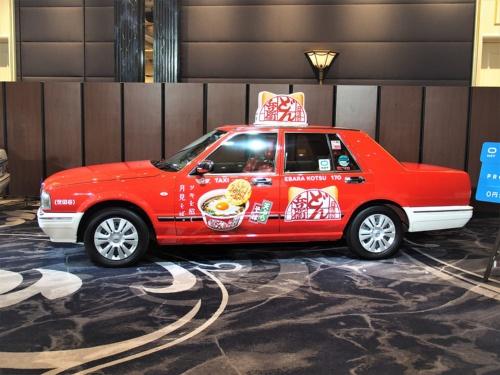 乗客の代わりにスポンサーがタクシー代を支払う「0円タクシー」。最初のスポンサーは日清食品で、対応するタクシーは同社の「どん兵衛」仕様にラッピングされている。2018年12月4日のディー・エヌ・エー発表会より(筆者撮影)
