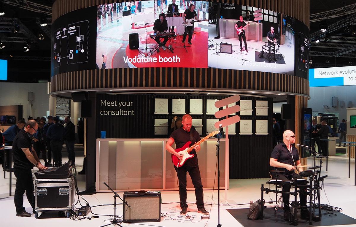 MWC 2019のボーダフォンブースとエリクソンブースを結んだ、5Gによる低遅延を生かしたライブセッションのデモ。ボーダフォン側のベースとキーボード、エリクソン側のギターとドラムのメンバーが同時に演奏し、音ずれのないセッションを実現していた。写真はMWC 2019のエリクソンブースより(筆者撮影)