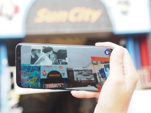 KDDIと沖縄セルラーが沖縄県沖縄市で実施した、VPSを活用した「AUGMENT」体験。街中で専用のスマートフォンをかざすと、同じ場所の昔の写真を見ることができる。写真は2019年11月23日の第27回「沖縄国際カーニバル」より(筆者撮影)